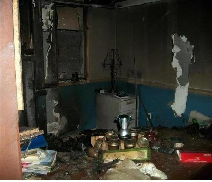 a room in a bedroom covered in soot and smoke damage after a fire
